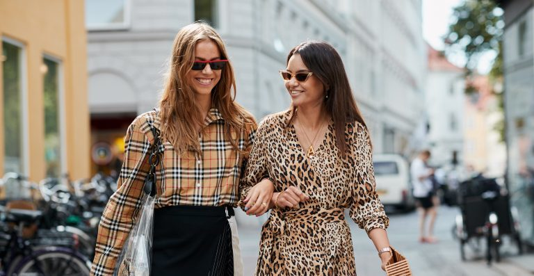 Two girls wearing a plaid top and a leopard dress