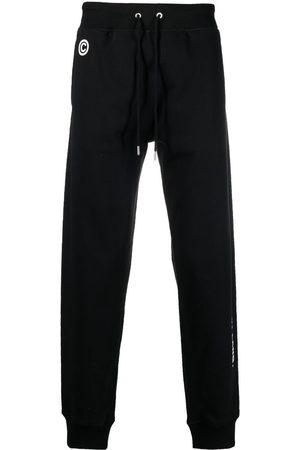 Helmut Lang Men Trousers - Impress slogan-print track pants